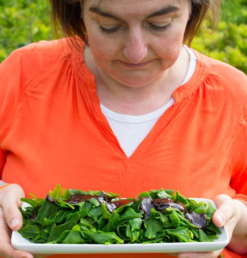 jaci holding a plate of warrigal greens with oyster sauce